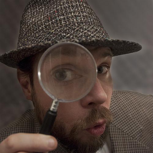 虫眼鏡を持つ探偵風の男性