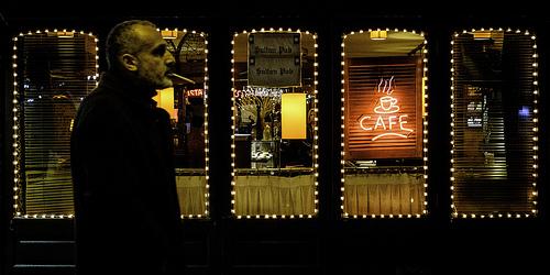 カフェの前で煙草を吸う男性