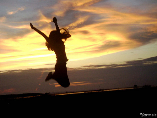 夕暮れ、ジャンプする女性