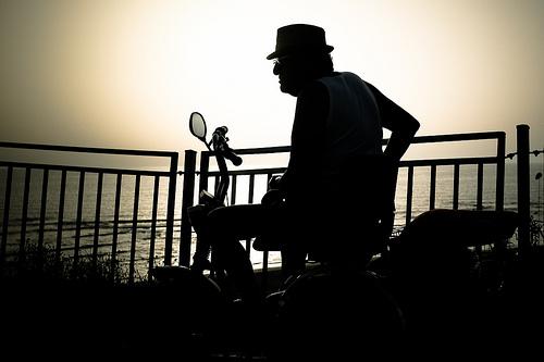 海岸でバイクに乗り、考え事をする男性