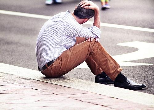 道端で頭を抱える男性