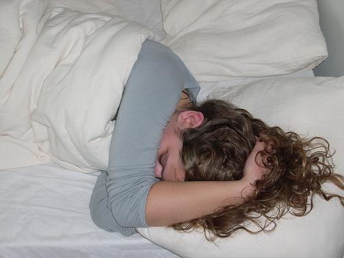 頭を抱えて寝る女性
